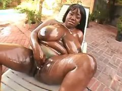 Fat oiled ebony plays with pussy
